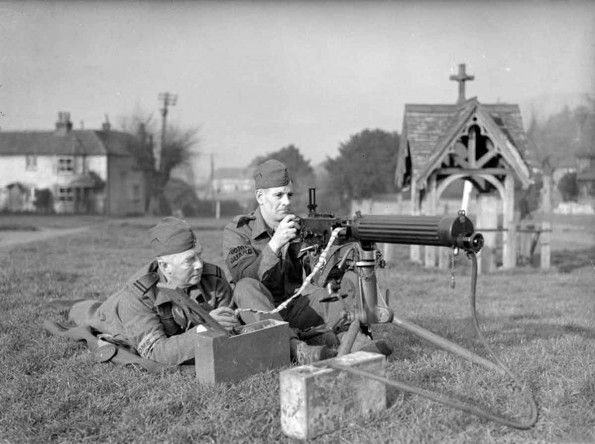 Two members of the British Home Guard with a Vickers machine gun on a village green in Surrey. Originally known as the Local Defence Volunteers, the force was set up in 1940 as a precaution against enemy parachute landings behind the lines in the event of an invasion. By July the Home Guard numbered 500,000.