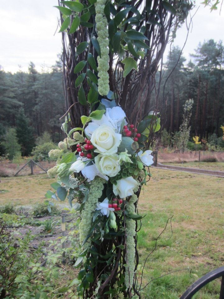 Rustic, willow arch with avalanche roses, skimmia and white lisianthus