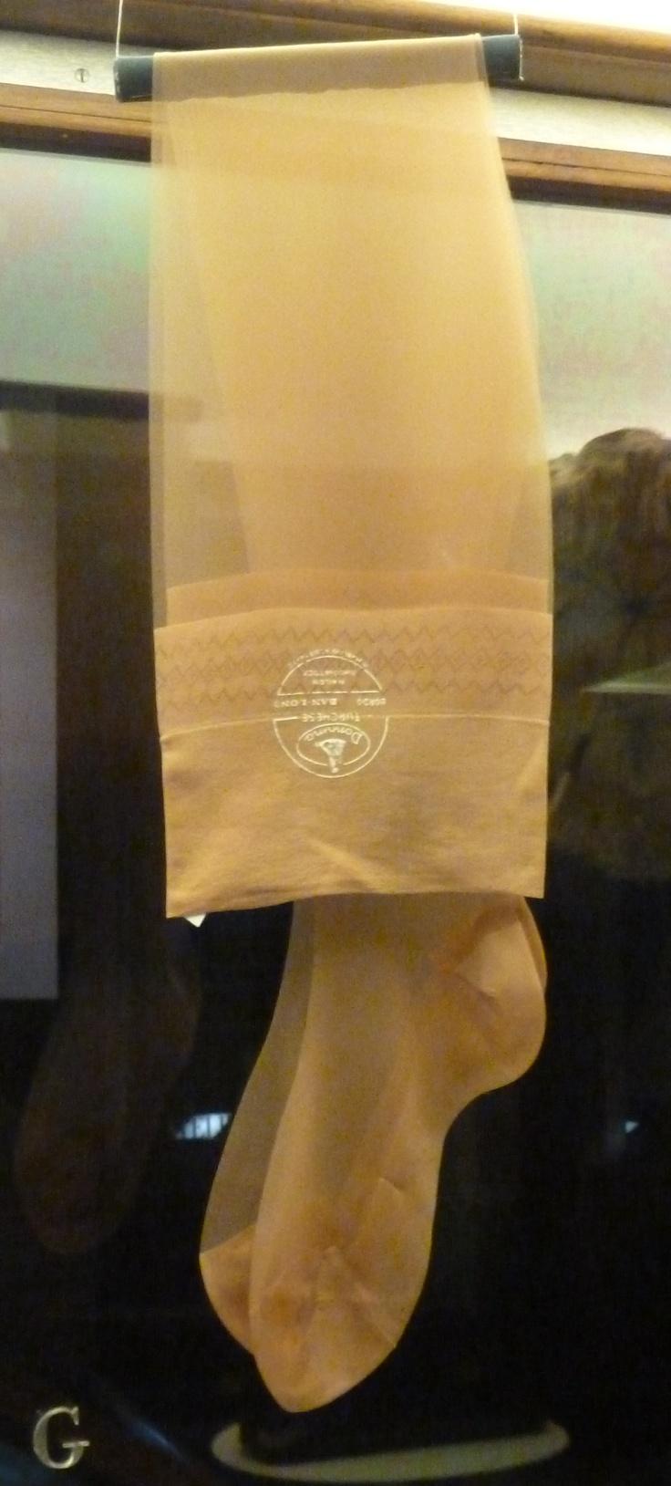 """N di NYLON  Calze femminili  Rhodiatoce, Piemonte, 1950-1960  Nailon Rhodiatoce  Collezione dell'Istituto Liceo Artistico Musicale """"Aldo Passoni"""", Torino  Il nylon fu brevettato nel 1935 negli Stati Uniti dalla Dupont e commercializzato dal 1938. Costituì una vera rivoluzione nella produzione tessile: prodotto di sintesi chimica, è estremamente sottile, leggero e resistente. In breve tempo sostituì la seta, molto costosa, per le calze femminili e si diffuse ampiamente nella lingerie."""