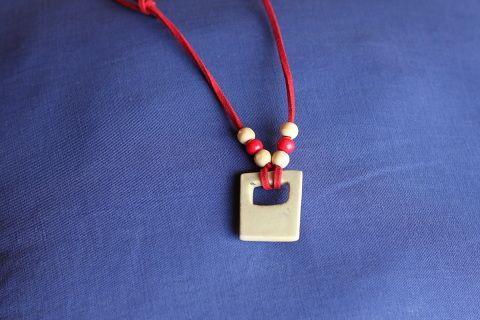 Grandeur  longueur maximum 12,5 pouces  - 32 centimètres    Collier pierre en  céramique  naturel avec appliqués superposés rouge et noir  fait à la  main  sur  corde suède  rouge  orné de perles de couleurs  naturel et rouge en bois.  Fermoir  noeuds coullissants.   Frais de livraison 5$ Merci de nous suivre sur Facebook  www.facebook.com/Creations-JOM-Céramiques-Bijoux-340093916336505