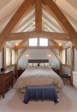 Beautiful bedroom space with full height ceiling and exposed timber frame. By Roderick James Architects.