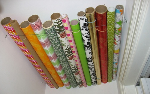 Hang your wrapping paper at the top of any closet with wire to save floor or attic space, love it!