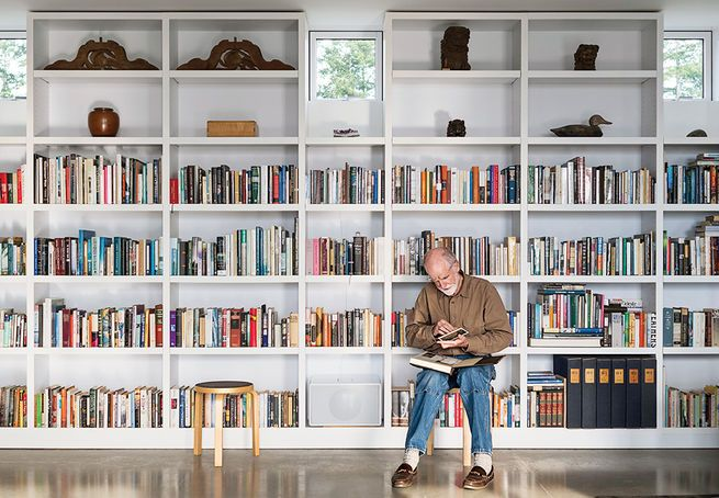 """A home built for an artist in the San Juan Islandsis specifically tailored to the resident. """"It's only what I need and no more,"""" he says. A wall of custom bookshelves stretches the length of the living area. Photo by: Eirik Johnson"""