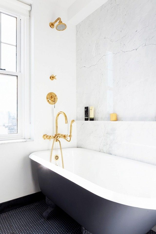 This petite bathroom doesn't need much to shine: simple hexagonal black tiles, a clawfoot tub, and aged brass fixtures. The marble backsplash wall finishes the space with a small built in...