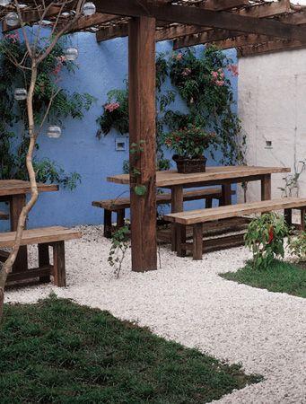 """Balcony // Varanda: """"Pedriscos levam ao pergolado. As refeições ao ar livre acontecem sob o pergolado de ipê neste quintal de 6 m². Para chegar a ele, passa-se pelo caminho de 1,20 m de largura coberto de pedriscos n° 3 (referência ao tamanho), da Cristiane Rodrigues Pedras Decorativas. """"Eles estão protegidos da terra por uma manta de drenagem de poliéster, que escoa a água."""""""