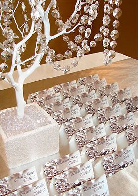 Place card table idea...  I like the white manzanita branch in the white wooden box wth the jewels hanging on the branches and in the box    (these place cards are god awful though! Haha)