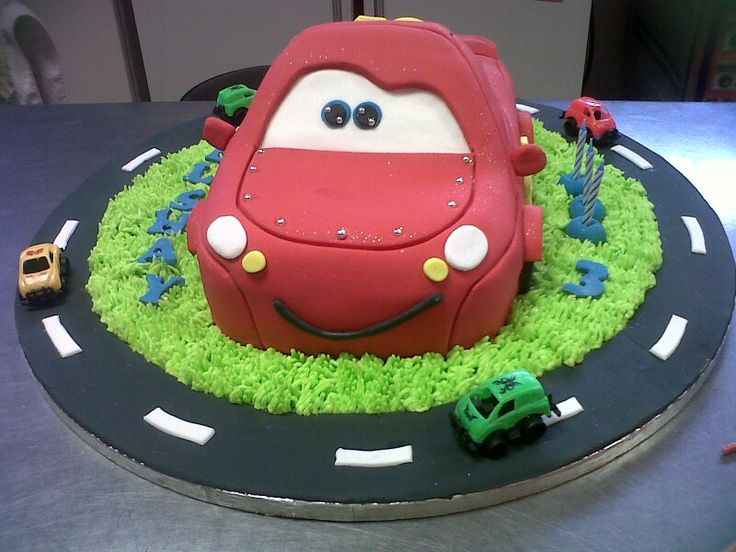 Lightning McQueen 3D cake with buttercream grass, fondant racetrack and toy cars. www.koekeloercakes.co.za