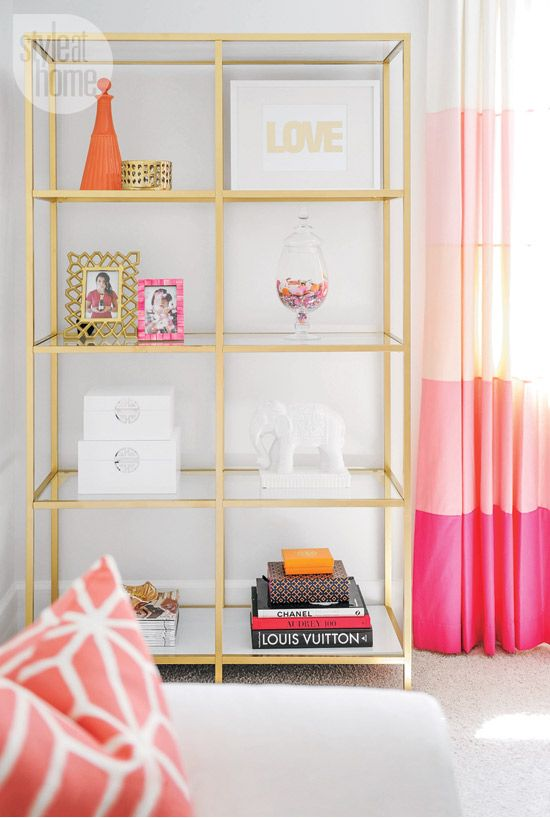 The gold étagère open shelves create a revolving display space for everything from personal photos to favourite books. Pink ombré drapes ...