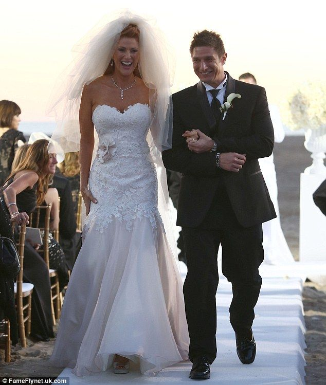 Just married! Pictures have been unveiled of Angie Everhart's November 5 wedding to Carl F...