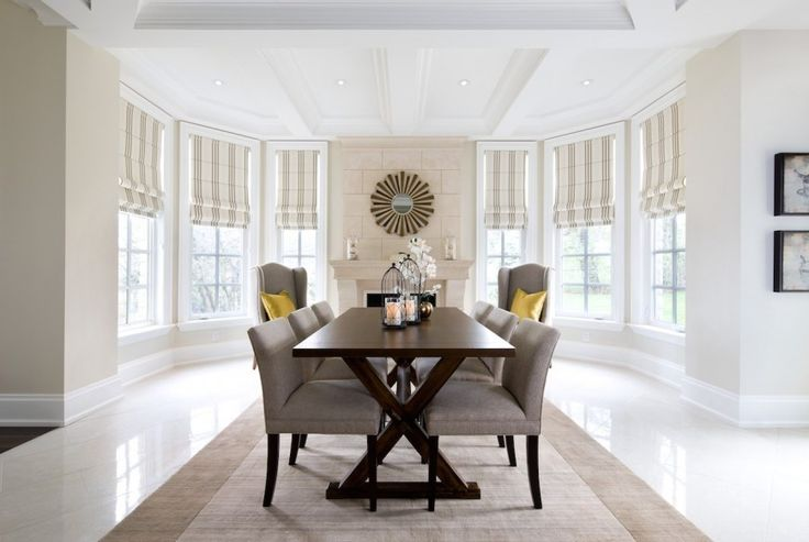 This light and airy dining area has a dark wood dining set in the center of the open-concept room. At the back of the curved room is a fireplace with a grand tile mantle.