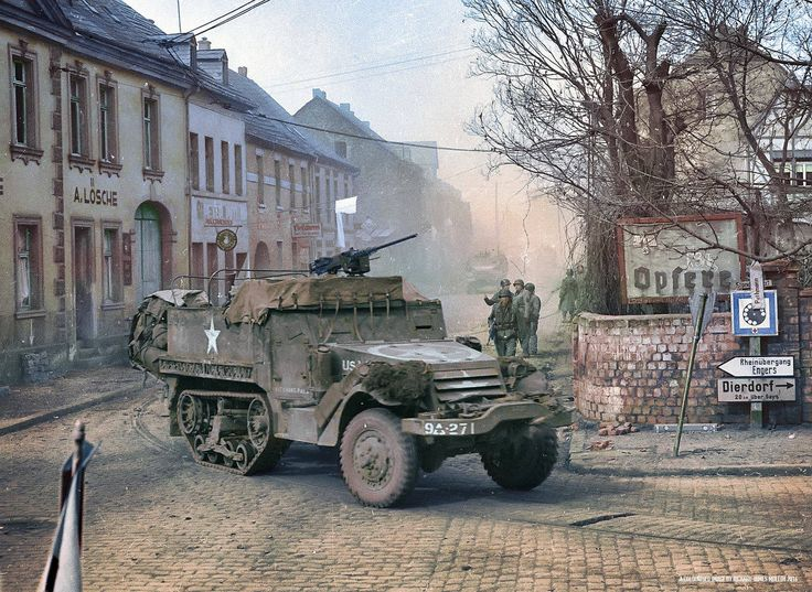 "An M3A1 Halftrack named ""Bitching Pals"" of 'B' Company, 27th Armored Infantry Battalion, 9th Armored Division, 1st U.S. Army, moves through Engers, on the right banks of the river Rhine in Germany. The town was heavily mined and caution in approach with armor was necessary. 27th March 1945. The M3A1 is armed with an M2 ""Ma Deuce"" .50 Caliber Machine Gun mounted on an M49 ring mount above the cab. 3m"