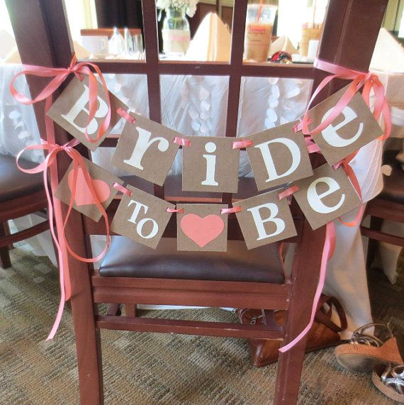 Bride  //  ♥ to ♥ Be  - Chair Sign Banner (3 x 3 inch size) (a little bit smaller of a size than the Standard 4 inch Full size Banners typically used to hang on the wall, but not as small as our 2.5 inch Mini size photo prop Banners, this way it fits nicely on the back of the Brides Chair!)  This Banner is created with KRAFT Chipboard Panels. IVORY Letters are attached securely to the square Panels. Choose the Heart Color and Ribbon or Twine Colors to coordinate with your Event by selecting…