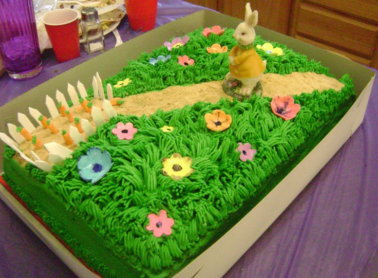 peter rabbit - 1/2 sheet cake with peter heading to his carrot garden . fence and carrots are fondant with grahm cracker crumb trail and a plaster figurine