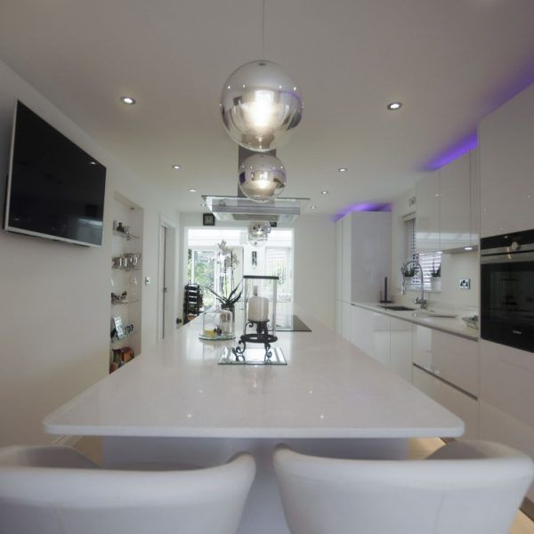 This stunning glossy kitchen features the Bianco Marmo Suprema quartz. This customer seems to like a white style decor and the worktops match perfect within the colour style. The purple lighting above the cabinetry really makes the white walls, worktops, stools and floors stand out. A perfect combination and a really lovely fantastic kitchen.