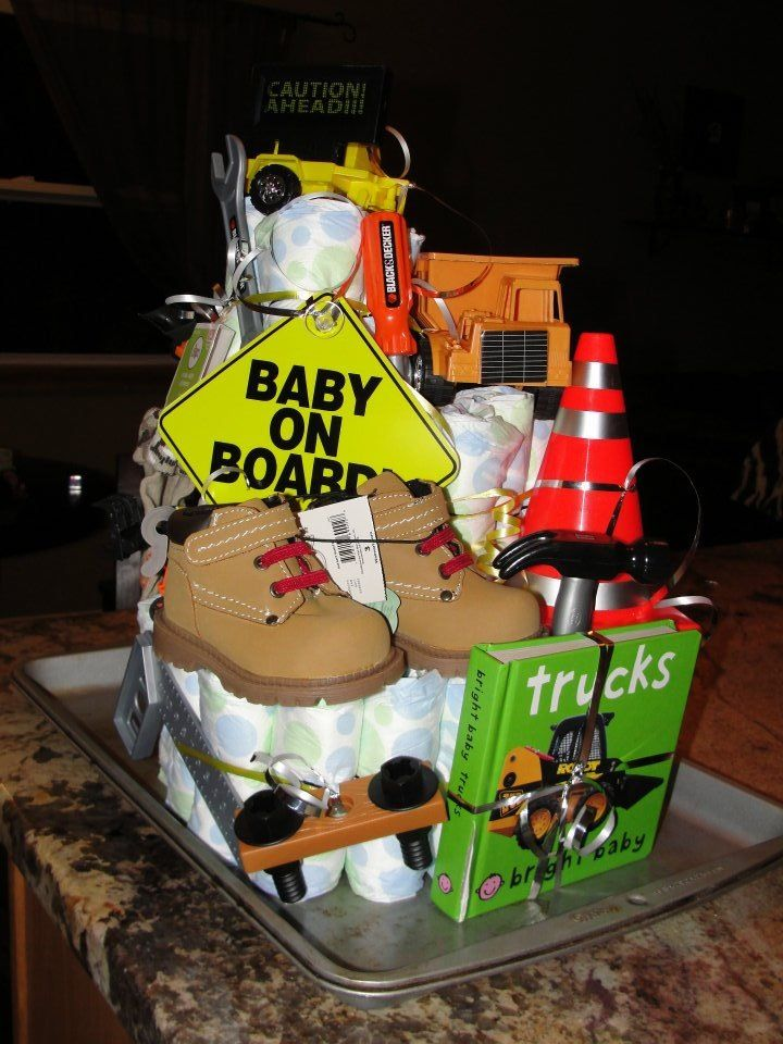 """I made this for my sister inlaw's baby shower that was a construction theme. Glorified themed diaper cake. Construction Trucks, work boots, tools, mini traffic cone, baby book about trucks and a blinking """"caution ahead"""" toy I found for the top. Get creative with it!"""