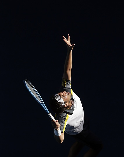 Marcos Baghdatis of Cyprus serves to Japan's Tatsuma Ito in their second round match at the Australian Open tennis championship in Melbourne, Australia, Wednesday, Jan. 16, 2013. (AP Photo/Rob Griffith)
