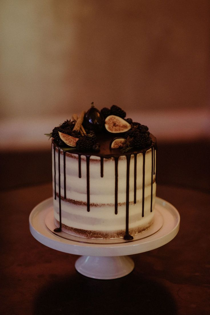A delicious naked drop cake with figs for our bride Charlotte.  Charlotte wore Houghton NYC modern off the shoulder full sleeve wedding dress for minimal modern London wedding at Asylum Chapel iconic London wedding venue.   Dress from Miss Bush luxury bridal boutique in Surrey, 20 minutes from London.  Image ©️ thekitcheners.co.uk