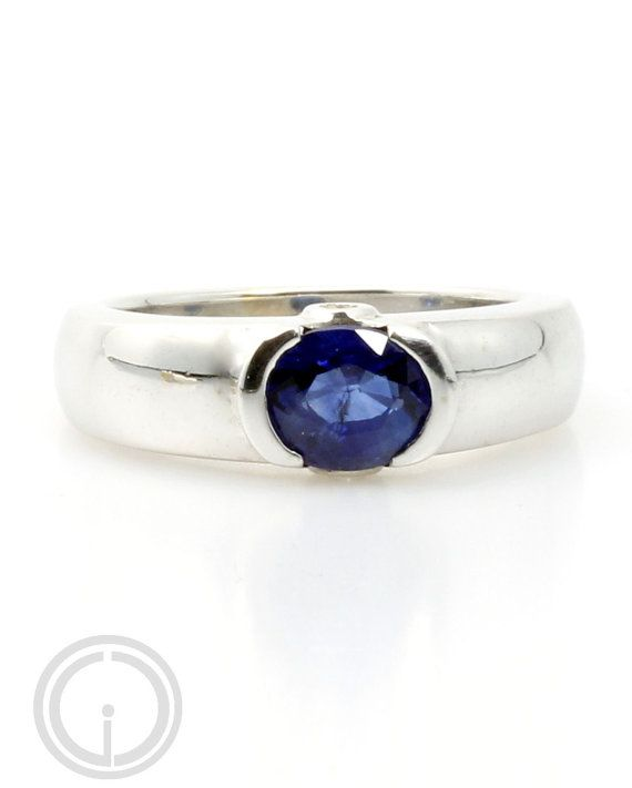 This is a substantial 18 kt white gold ring set with a beautiful natural blue sapphire. This would make a great engagement ring alternative to the typical diamond ring.    The natural blue sapphire measuring approx 7 x 5.9 mm is bezel set east/west instead of the usual north/south setting. You will find 2 SI clarity round brilliant cut diamonds measuring approx 1.4mm with an estimated total weight of 0.025cts set on either side of the bezel.  The mount is 18 kt white gold, tapered f...