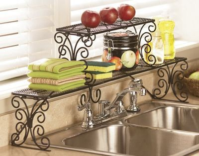 """Dress up your kitchen's busiest work area with our 2-tier Scrolled Over-the-Sink Shelf. Two tiers provide plenty of room for soap and scrubbies and space for special touches like a bud vase or small houseplants. Fits single and most double sinks. Wrought iron with rust-resistant finish. Easy three-step assembly. 36"""" w x 14"""" h x 6"""" d."""