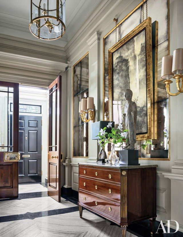A fifth-century Chinese lohan figure stands on an antique Northern European commode from Newel in the entrance hall   archdigest.com