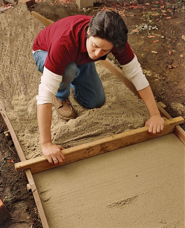 Step 5: Install side guide rails and fill with 2 inches of masonry sand or stone dust, tamping and smoothing it with a screed.