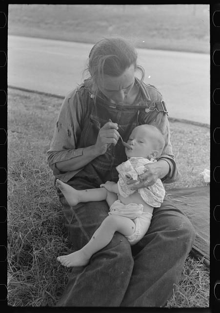 Lee, Russell (1903-1986), 1939 June. Migrant mother feeding her baby while the family was stopped by the roadside for lunch, east of Fort Gibson, Muskogee County, Oklahoma