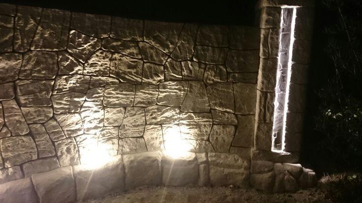 Pilar iluminado y muro curvo en hormigon vertical estampado
