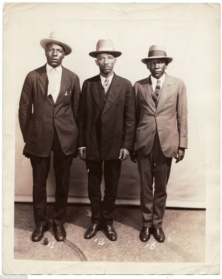 Sharp-dressed men in three-piece suits and top hats stand for their arrest photo and are i...