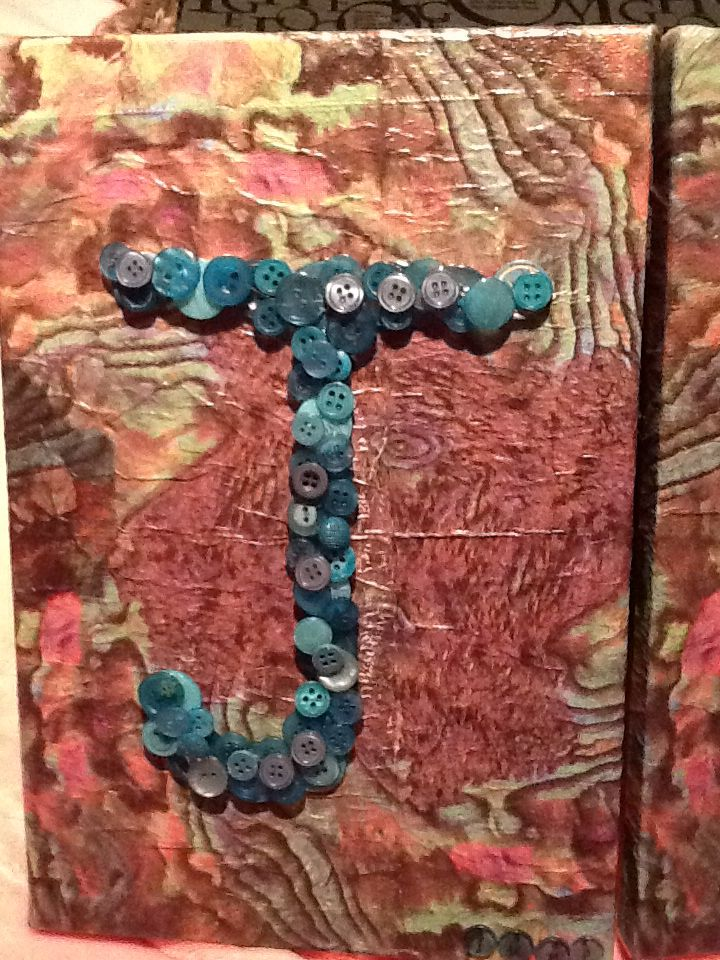 Button art.  Initial 'J' made for my Aunt (June). Buttons glued onto art canvas covered with printed paper napkin (NZ Paua shell pattern).