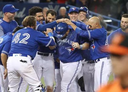Kendrys Morales of the Toronto Blue Jays is congratulated at home plate by teammates after hitting a game-winning solo home run during MLB action against the Baltimore Orioles at Rogers Centre on April 15, 2017.