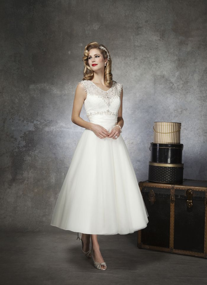 Justin Alexander wedding dresses style 8650 This gown features a beaded, Chantilly lace, modest V neck, and is  accented by a silk dupion cummerbund on a tulle tea length ball gown.  Buttons cover the back zipper and finish at the end of the cummerbund.
