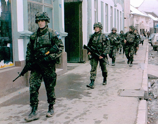 Soldiers from Company A, 1st Battalion, 18th Infantry, and the Danish Battalion of the Nordic-Polish Brigade [NORDPOL], patrol Brcko, Bosnia, February 7, 1997. SFOR stabilization forces included soldiers from Poland, Russia and Turkey, as well as the Nordic countries. They separated the former warring forces to keep the peace.
