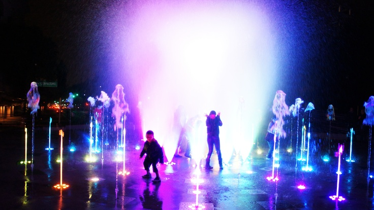 children playing in the water jets of the fountain