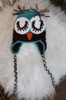 Owl hat with ear flaps, braided tassels and sleepy eyes. Custom order for colour and size needed $25.00. Visit Angelmouse Knitwear on Facebook