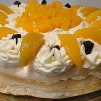 Tort bezowy z bitą śmietaną i brzoskwiniami