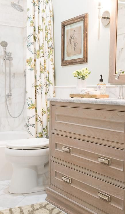 Small beach style bathroom is fitted with a cream and gray colored bath mat placed in front of an antique gray washstand completed with drawers adorning polished nickel pulls and a carrera marble countertop finished with a sink and polished nickel faucet fixed beneath an antique gray oak vanity mirror.
