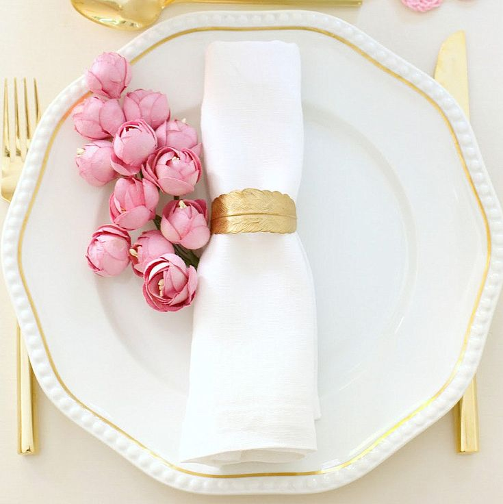 gold feather napkin ring, gold flatware, pink roses.