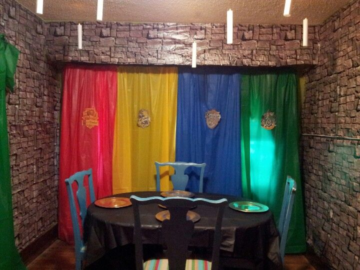Over the top dining room decorations for our Harry Potter party. Floating candles, house colors, and gold chargers. Never underestimate the power of $1 plastic tablecloths!