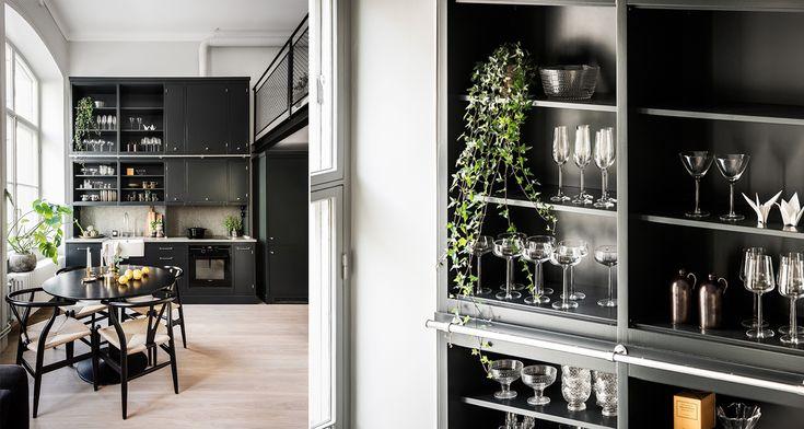 Svart kök och loft. Trendiga designstolar och växter. Öppen köksförvaring.