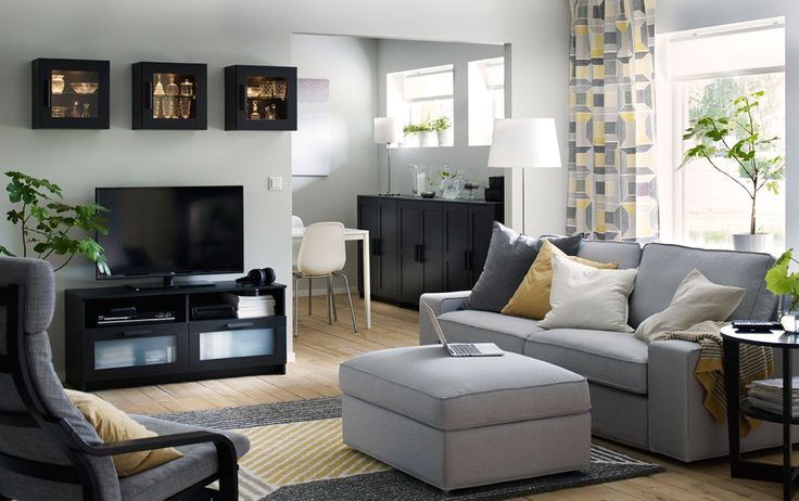 Black TV bench, wall cabinets and free-standing cabinets in a white, yellow and gray livingroom.