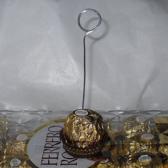 48 Wire card holders for table number or name tags made for Ferrero Rocher Chocolates.  I buy the box of 48 Ferrero Rocher Chocolates at Sams Club .... If you wish less or more message me for a price. I love these cause the base [not included] is that extra special treat for your guest. They are great for weddings, dinners, birthdays and just because .......  I use Aluminum Jewelry wire to make these and I hand bent them with my own two hands so I give personal attention to each and every…