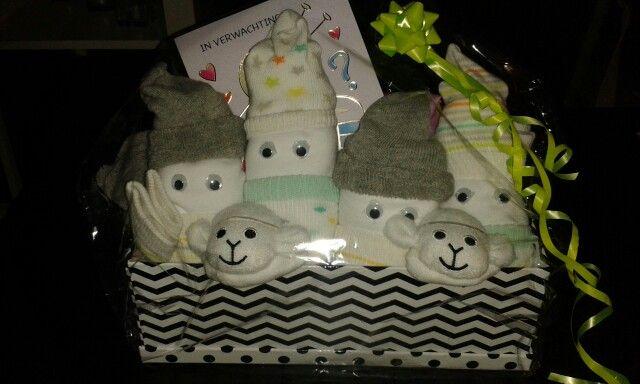 Een hervulbare kleenex doos gevuld met opgerolde rompertjes. De sokjes zijn gebruikt als mutsje en slaapzakje. De wiebeloogjes zijn bevestigd met dubbelzijdige plakband. De rest is aangevuld met de overige sokjes.