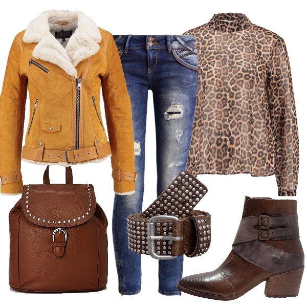 In questo outfit lo stile rock, rappresentato dal chiodo giallo e dagli accessori con le borchie, è mixato all'animalier della blusa. Il risultato è un look audace e innovativo.