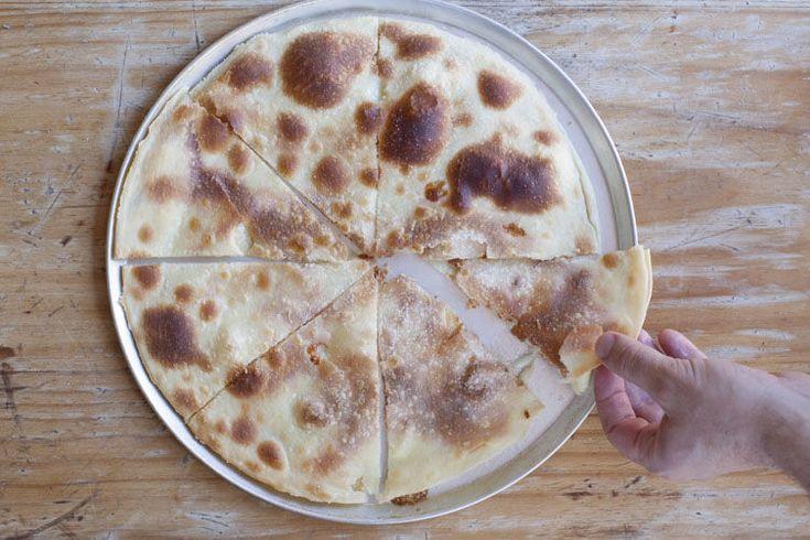 Focaccia di Recco (cheese-filled focaccia).  Breakfast in Liguria, Italy.