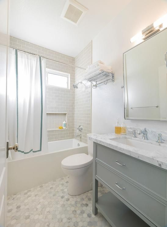 Gray and white bathroom features floors clad in carrera marble hex tiles that lead to a modern drop in tub concealed behind a white and gray order shower curtain and fitted with a polished nickel shower kit mounted on gray subway surround tiles framing a window and a tiled niche.