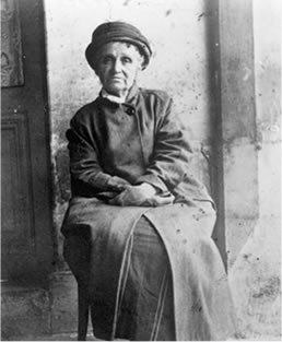 Photo de Camille Claudel, assise sur une chaise, à l'asile de Montdevergues