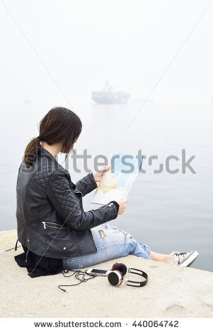 A beautiful woman tourist with map on port