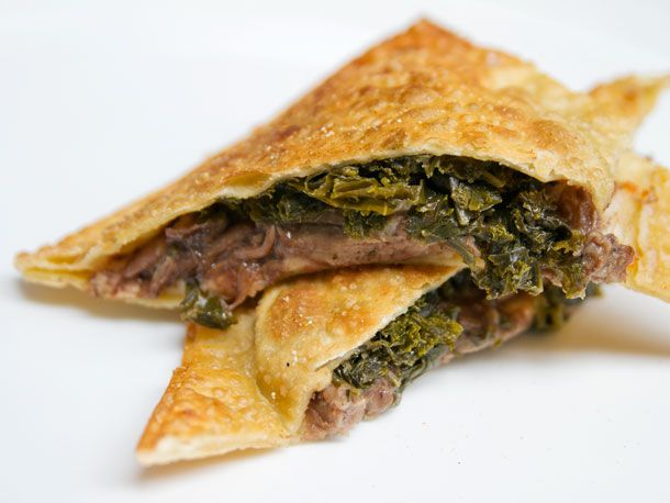 Lamb Hot Pocket  Piled high with red wine-braised lamb. A layer of creamy and tangy goat cheese-potato purée is spread on the bottom of the pocket, and the lamb is topped with sautéed kale and shallots, an earthy tangy touch of green.