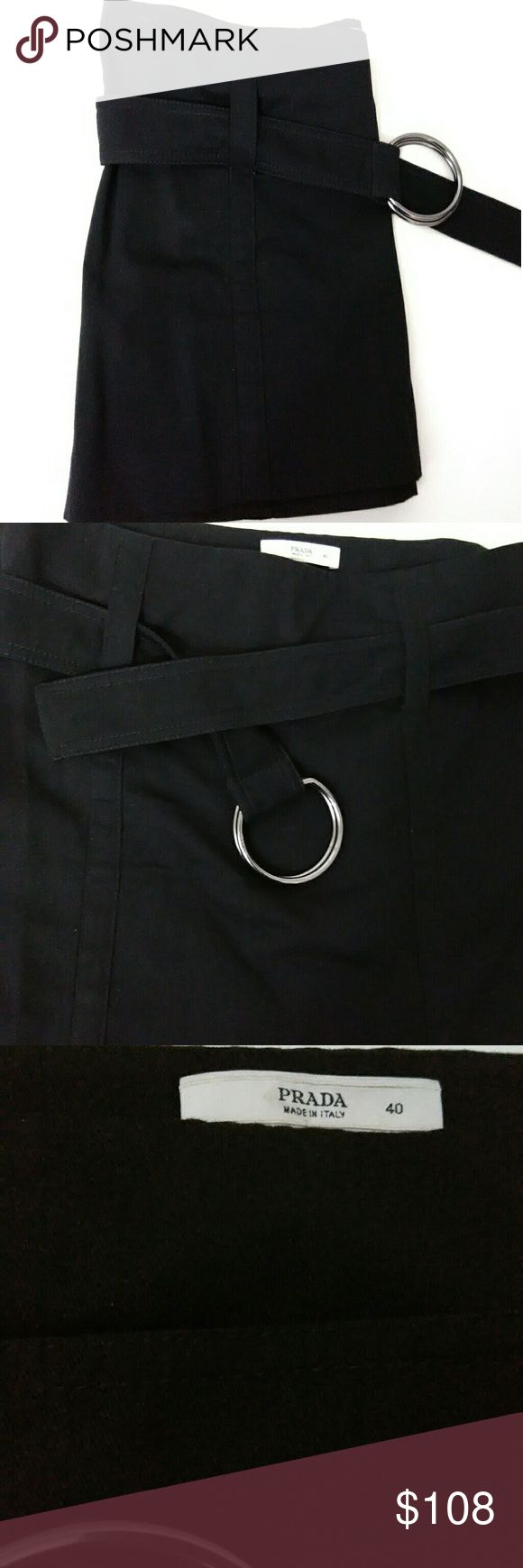 """PRADA Black Skirt Size 40 Very elegant Authentic Prada Black Skirt. Size is women's 40 Made in Italy 100% cotton. Approx measurements are Hip 16"""" and Length 13.5  This skirt is a very dark black ,it is not faded at all . I am really unsure if this was ever worn , it is like New. The skirt features a black belt with 2 rings to secure it. Each ring is silver in color and has """"Prada"""" stamped into it . Skirt has zipper on side. RN 98339 Prada Skirts"""