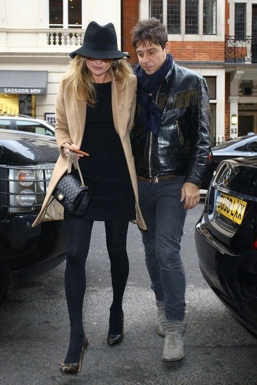 Kate Moss in Camel coat over black dress+black fedora hat+black chanel bag+black tights+black printed pumps